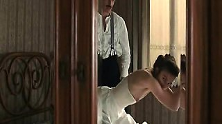 Keira Knightley bent over the arm of a sofa with her top