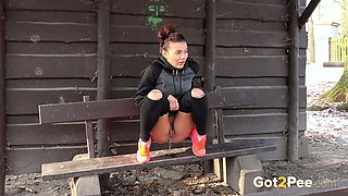 Sporty brunette white young chick in the park pisses on the bench
