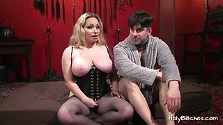 Big breasted blonde mistress is giving her slave a handjob