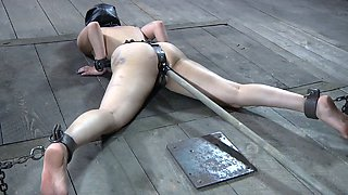 Sex slave in rubber mask is fucked on the floor with long stick