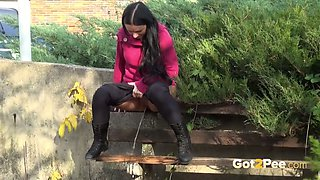 Long haired naughty sinful brunette sits on the bench and pisses