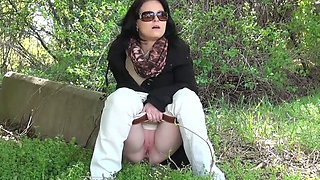 Slutty brunette in sunglasses enjoys pissing on the grass