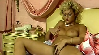 Mesmerizing busty blonde milf on the bed blows her tits
