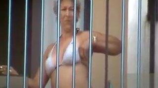French mature in a bikini smokes on her deck