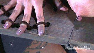 Red-haired dominatrix sticks needles under her slave's fingernails