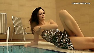 Long legged white girl in evening dress dips in the water